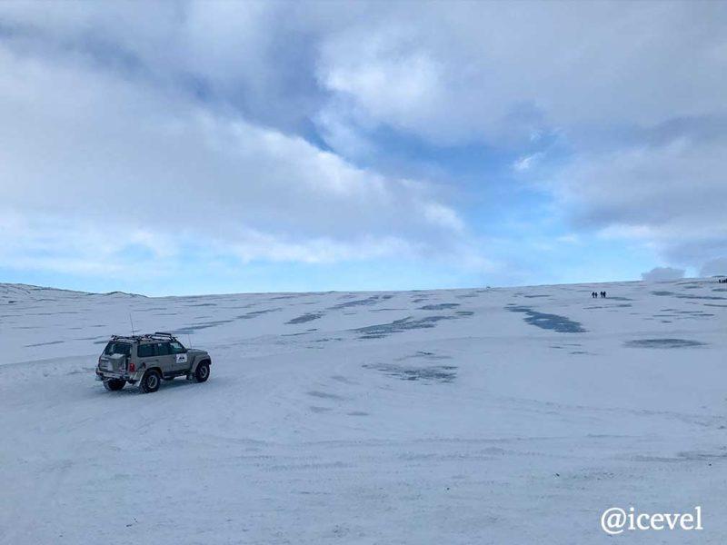 スーパージープと氷河の上をハイキングしている人たち